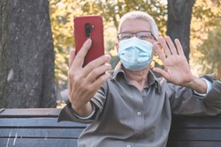Senior old woman sending love and kisses to her family over social media apps using her cellphone, with a mask on