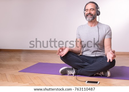 Senior older man practicing yoga and listening to his favourite relaxation music