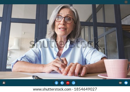 Senior older middle aged business woman teacher, remote tutor, distance coach talking to camera at virtual meeting web conference video call chat working online. Videocall app screen web cam view.