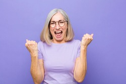 senior or middle age pretty woman shouting triumphantly, laughing and feeling happy and excited while celebrating success