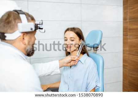 Senior otolaryngologist examining ears with ENT tuning fork for a young patient in the medical office. Hearing test with tuning fork concept Foto stock ©