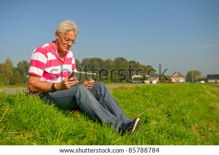 Senior outdoor in nature landscape with tablet PC