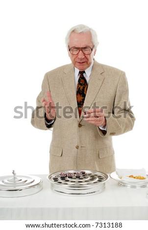Senior pastor praying over the communion wine. - stock photo