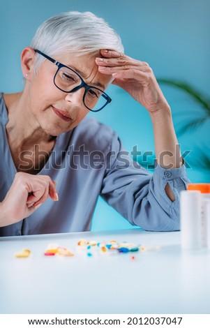 Senior patient failing to follow medical advice, demonstrating prescribed medicine non-adherence behavior Stock photo ©