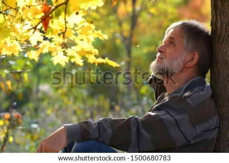 Senior pensive man is sitting under a tree