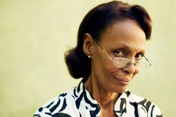Senior people and confidence, portrait of proud african american woman with glasses smiling and looking at camera. Copy space