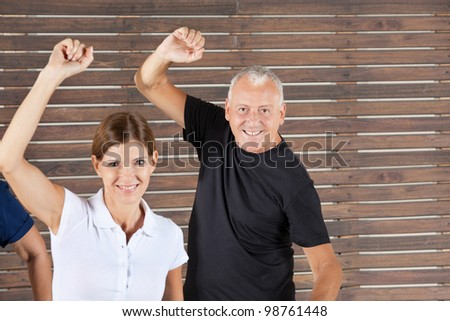 Senior people moving in dancing class in a group