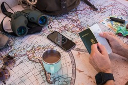 Senior people planning vacation trip on a world map checking passport. Money and travel accessories - active retired elderly concept