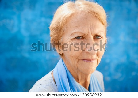 Senior people portrait, happy old blonde woman in blu clothes smiling and looking at camera against blue wall