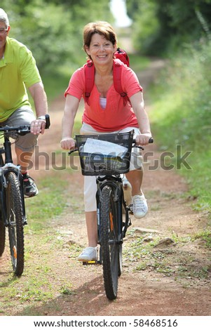 Senior people riding bicycle in the countryside
