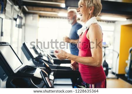 Senior people running in machine treadmill at fitness gym club
