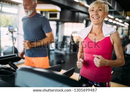 Senior people running on a treadmill in health club.