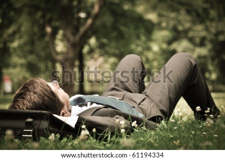 Senior people series - mature business man lying on grass and relaxing in green park - stock photo