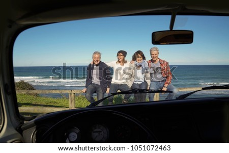 Senior people traveling with vintage camper van by the ocean