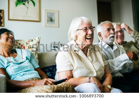 Senior people watching televison together