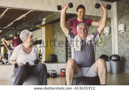 Senior people workout in rehabilitation center. Senior people with personal fitness trainer.  stock photo