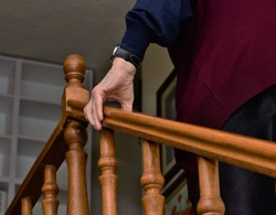 Senior person is climming stairs while wolding hand rail for support