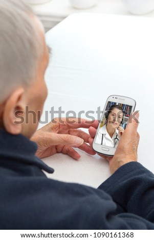 Senior person sitting with her smartphone at a table having a video call with her doctor, modern lifestyle concept