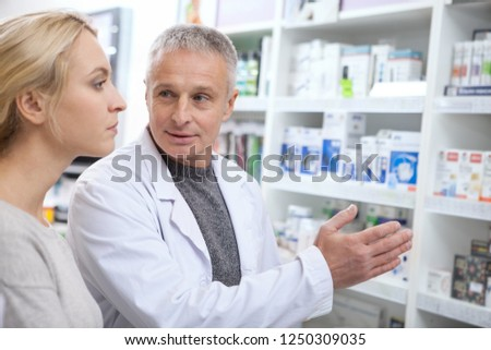 Senior pharmacist helping his female customer choosing prescription drugs from the shelf. Young woman shopping at drugstore, taking advice from mature chemist. Consumerism, friendly staff concept