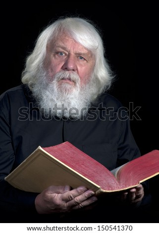 Senior Priest with white beard and Bible Book
