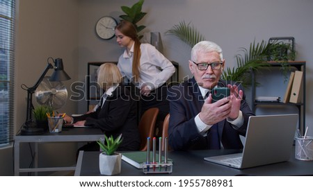 Senior professional businessman grandfather company director in modern office interior using mobile phone texing message working watching video successful people communicating. Elderly freelancer man Photo stock ©