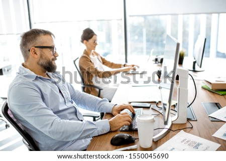 Senior programmer working on the computer in the modern office with coworkers on the background