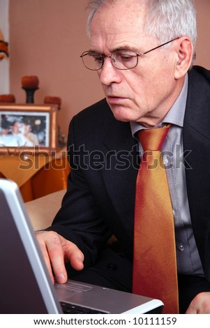 Senior real estate agent looking at his laptop
