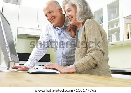 Senior retired couple at a desk using a computer and looking at the screen together