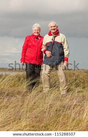 Senior retired couple man and woman enjoying outdoors. Dune landscape with blue cloudy sky. Texel. Wadden island. The Netherlands.
