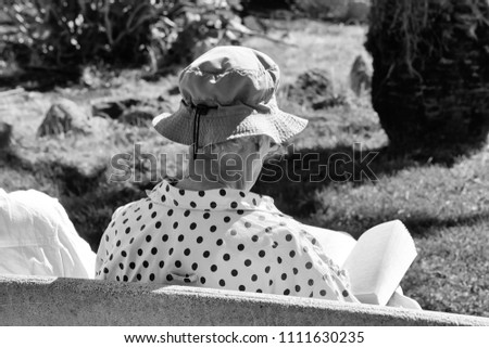 93891ac8f5ae4 Senior retired woman in grey bucket hat reads book sitting on park bench  outdoors on sunny