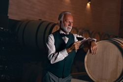 Senior rich man leaning against a wooden barrel savoring red wine in his wine cellar