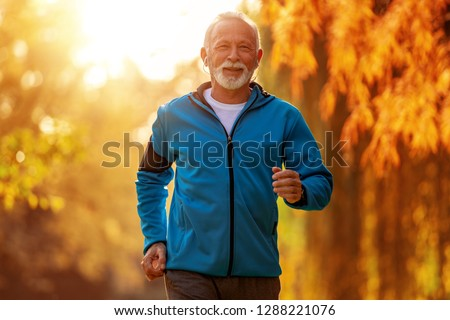 Senior runner doing stretching in autumn park. #1288221076