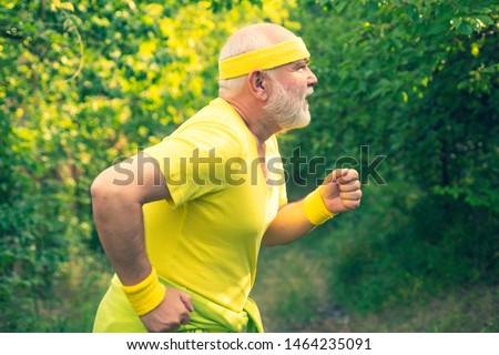 Senior runner in nature. Cardio workout. Running in park in the morning. Senior male is enjoying sporty lifestyle. Healthy lifestyle concept.