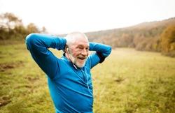 Senior runner with armband doing stretching. Autumn nature.