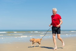 Senior runner with dog at the beach