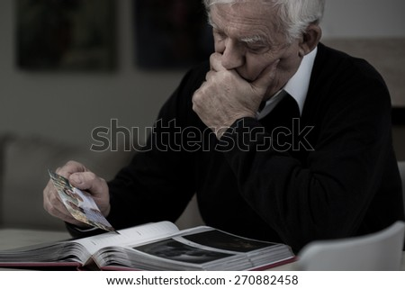 Senior sad man with photo missing his wife