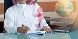 Senior Saudi Businessman Hand Writing At His Desk with Laptop