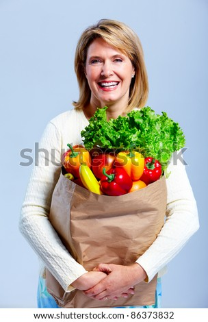Senior shopping woman with grocery items . Over grey background.