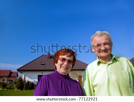 Senior smiling couple in front of their new house