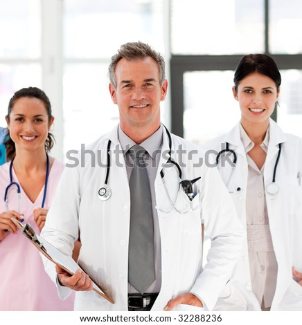 Senior Smiling doctor with his colleagues in front of the camera