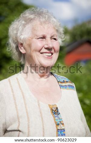 Senior smiling woman looking away in garden