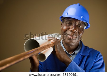 Senior South African or American plumber with pipes - stock photo