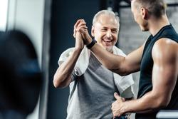 senior sportsman giving highfive to trainer in sport center