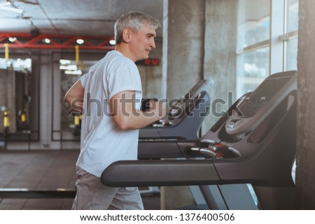Senior sportsman running on a treadmill at the gym, copy space. Healthy elderly man enjoying working out at sport studio, jogging on a running machine. Cardio, endurance, health concept