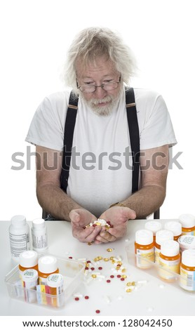 Senior staring down at prescriptions with a hanful of pills isolated on white