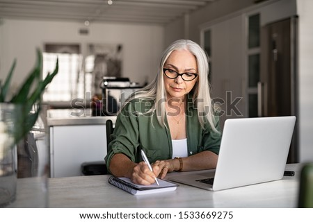 Photo of Senior stylish woman taking notes in notebook while using laptop at home. Old freelancer writing details on book while working on laptop in living room. Focused cool lady writing notary in notepad.