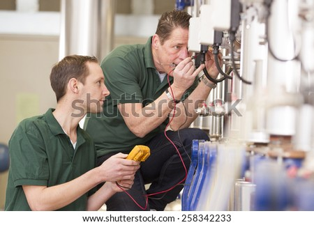 Senior technician and junior technician repairing agriculture machinery in a greenhouse #258342233