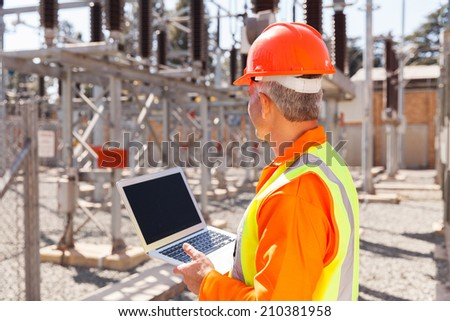 senior technician holding laptop computer in substation