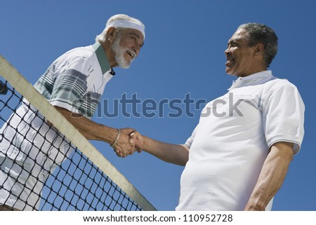Senior tennis players shaking hands against clear sky