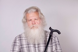 Senior thickset Caucasian man with splendid grey hair and beard on grey background, looking in camera with troubled face and holding gimp stick. Attractive elderly European handsome people close up.